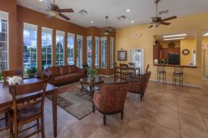 Lounge area with seating, kitchen area and ceiling fans